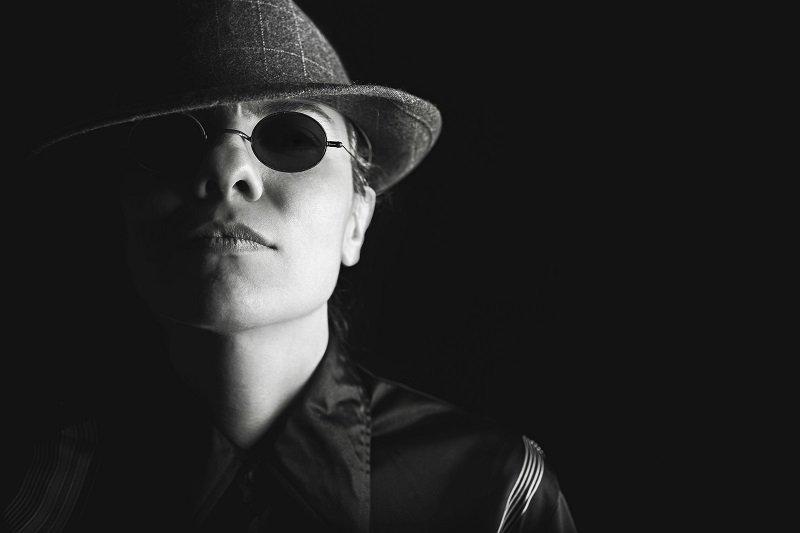 Imagen de una persona, en blanco y negro, con sombrero y lentes oscuros